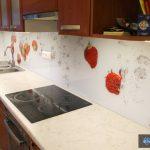Rdeče jagode v vodi na kuhinjskem steklu
