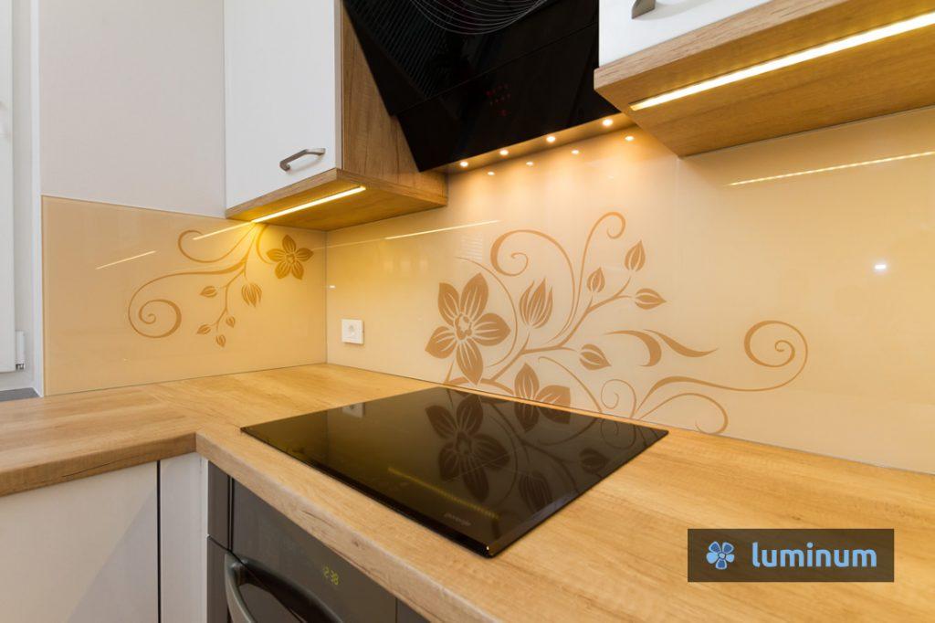 Steklena kuhinjska stenska obloga (t.i. kuhinjsko steklo) v rjavih barvah kuhinje z nežno grafiko cvetov in vitic