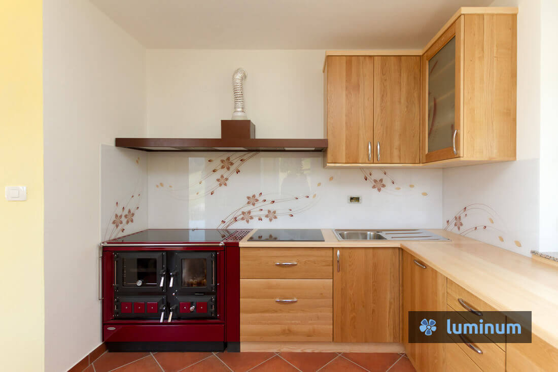 Belo kuhinjsko steklo s personaliziranim motivom rdečih rožic in vijug, vgrajeno poleg štedilnika na drva