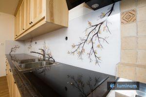 Kuhinjsko steklo z motivom veje z rjavimi listi, ki se barvno ujema z masivno leseno kuhinjo in vgrajenim štedilnikom